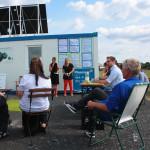 Katrin Schwahlen und Dany Krohne vom Pionierprojekt basis.wissen.schafft e.V. begrüßen das Publikum zur Einweihung der Solarmodule am Wissenscontainer auf dem Tempelhofer Feld in Berlin